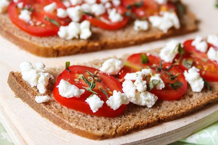 Two pieces of bread with goat cheese bruschetta spread on them.