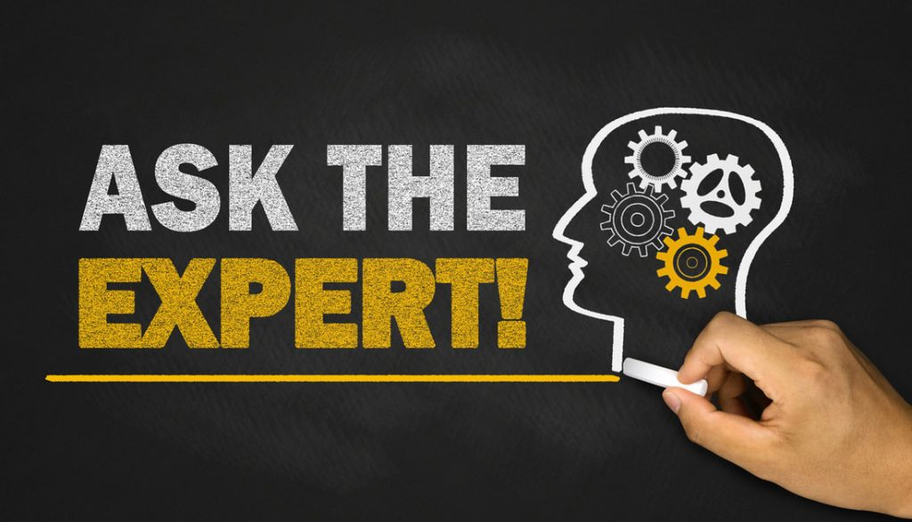 "The words ""ask the expert"" are written on a blackboard next to human head with gears depicted as the brain."