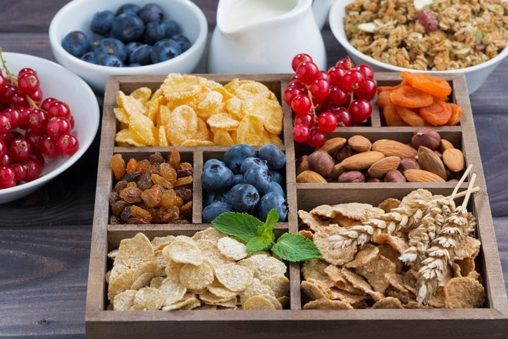 A picture of crackers, almonds, cherries, blueberries, and other healthy diet snacks.