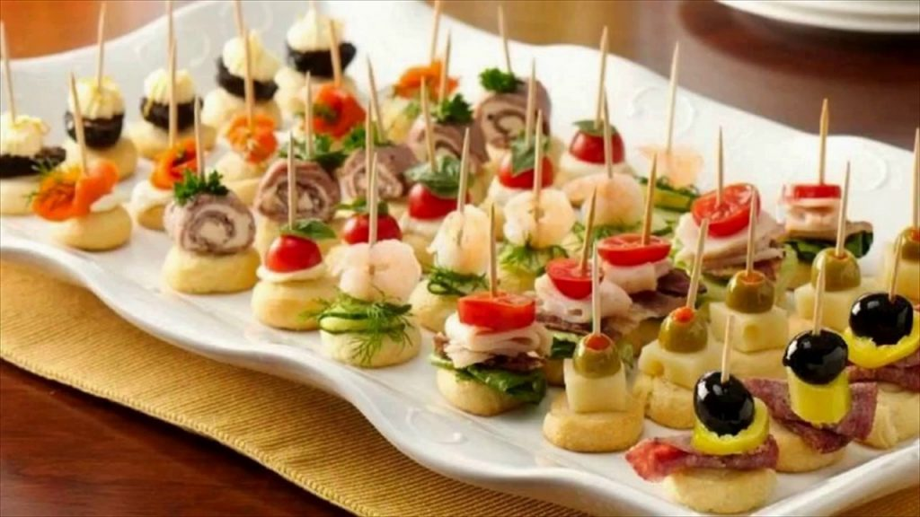 A tray of meats, cheeses, olives, and other finger food snacks.