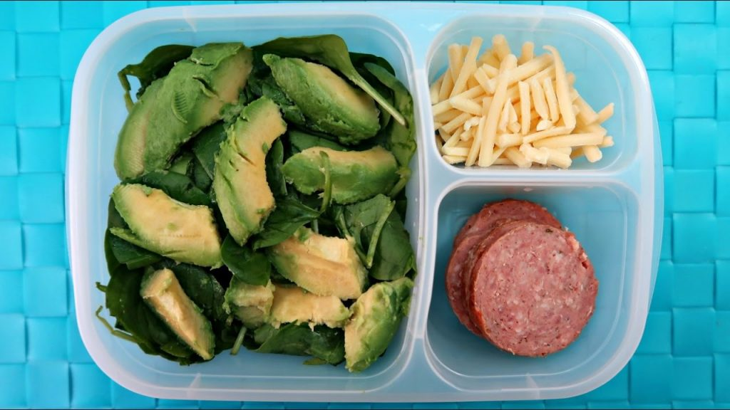 A container with avocado, cheese, and summer sausage, all keto snacks.