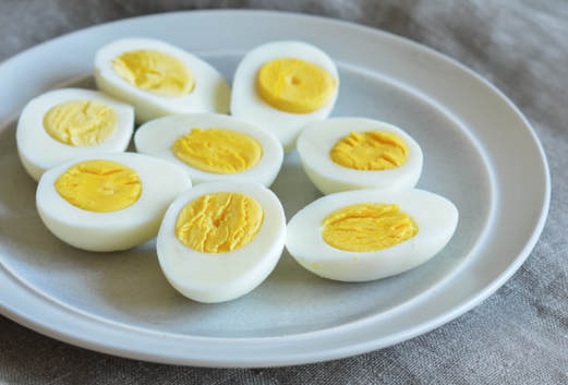 A plate of hard-boiled eggs sliced in half.