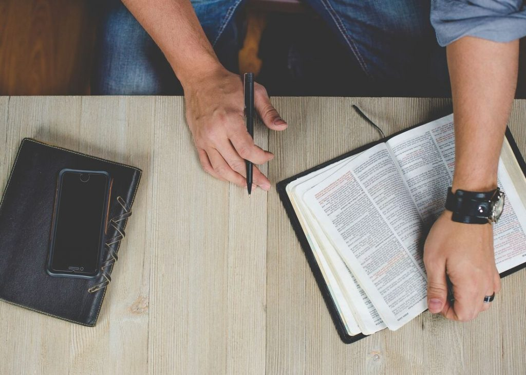 A person holding a Bible and a pen.