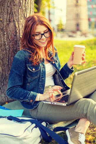 Smiling redhead teenager in eyeglasses with laptop computer