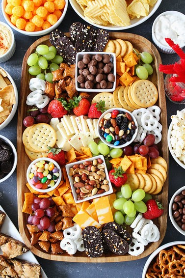 A snack board filled with cheese, grapes, candies, pretzels, and other sweet and salty snacks.