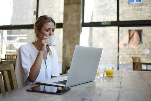A woman working remotely, sipping her coffee at her laptop