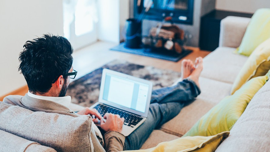 A man working remotely from his couch using a laptop